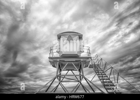 Low angle view of a lifeguard tower against a cloudy sky. Black and white image. - Stock Photo