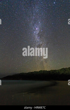 Milky way galaxy with southern cross constellation seen from sandy beach in Australia. Image contains noise and - Stock Photo