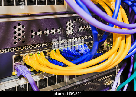 Data centre patch panel with patch cords connected to power over ethernet ports of switch mounted into the secure - Stock Photo