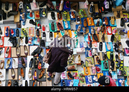 Barcelona, Spain - March 02, 2016: Woman browsing the large variety of shoes on offer at a flea market stall at - Stock Photo