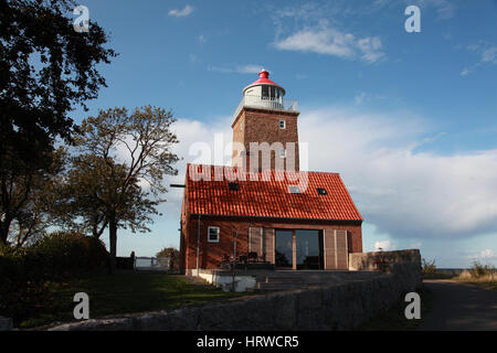Svaneke lighthouse on the Baltic island of Bornholm, Denmark with modern holiday accommodation to rent - Stock Photo