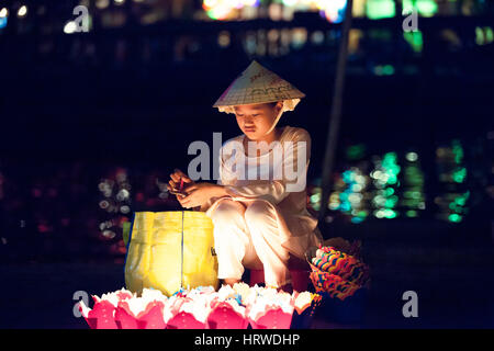 Hoi An, Vietnam - March 14, 2014: Vietnamese girl in conical hat selling candles for tourists at night. - Stock Photo