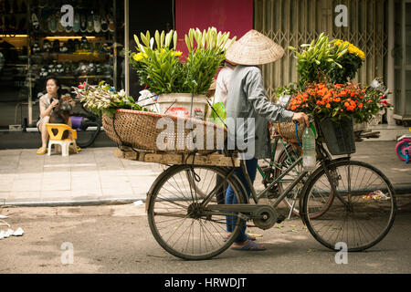 Hanoi, Vietnam - May 12, 2014: Two women flower vendors in conical hat with bicycle having a conversation on the - Stock Photo
