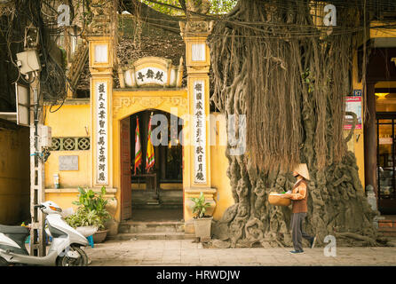 Hanoi, Vietnam - April 25, 2014: Vietnamese woman in conical hat with basket in hands is passing by the temple on - Stock Photo