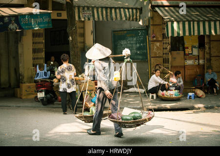 Hanoi, Vietnam - 26 April, 2014: Woman vendor carrying baskets with fruits on the street of Hanoi on 26 April 2014, - Stock Photo