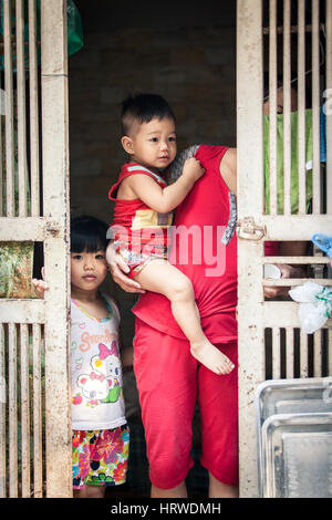 Hanoi, Vietnam - April 26, 2014: Portrait of  Vietnamese family at the entrance of their home on the street of Hanoi, - Stock Photo