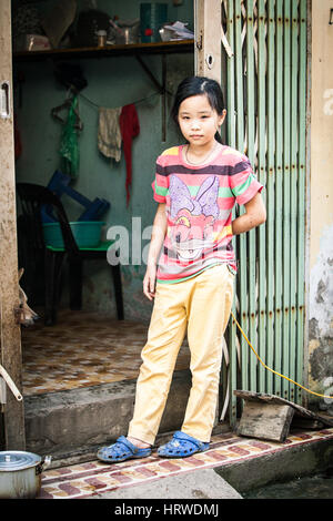 Hanoi, Vietnam - April 26, 2014: Portrait of  Vietnamese girl with dog at the entrance of her home on the street - Stock Photo