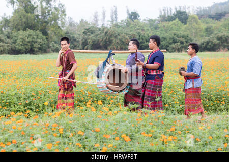 young men marching with drums in traditional costumes on the Thai countryside - Stock Photo