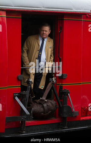 A re-enactor in vintage Royal Mail uniform waits for departure on a demonstration run of the Travelling Post Office, - Stock Photo