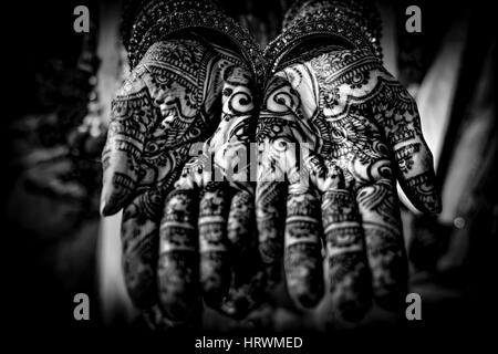 The painted hands of an Indian bride, known as Mehndi - Stock Photo