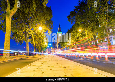Cityscape of a Street in Westminster with Big Ben in the distance at night - Stock Photo