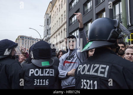 Berlin, Germany. 4th Mar, 2017. Left wing protesters blocked by policemen, are gesturing towards right wing protesters - Stock Photo
