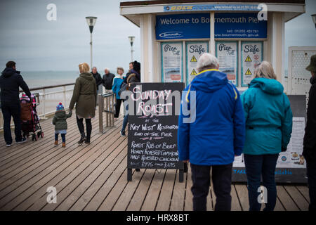 People walk along Bournemouth Pier on a winters day in Dorset, UK. - Stock Photo