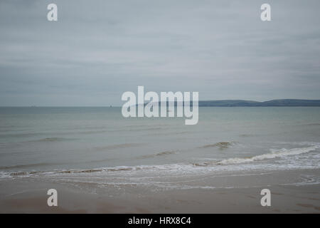 A gloomy and overcast day on an empty sandy beach at Bournemouth, Dorset, UK. - Stock Photo