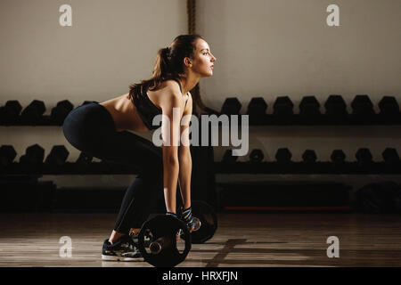 fitness woman weightlifting deadlift. Fitness model girl weightlifting in gym. - Stock Photo
