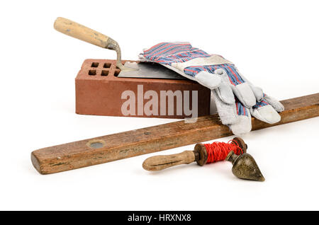 Old construction accessories trowel, bricks, plummet and level on white background. - Stock Photo