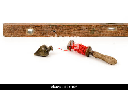Old level tool and plummet isolated on white background - Stock Photo