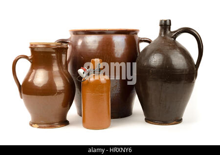 Old stoneware bottles and clay jug isolated on white background - Stock Photo