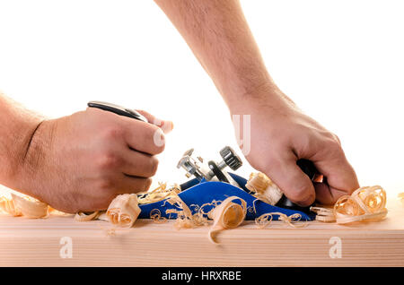 Carpenter working with planer on wooden plank - Stock Photo