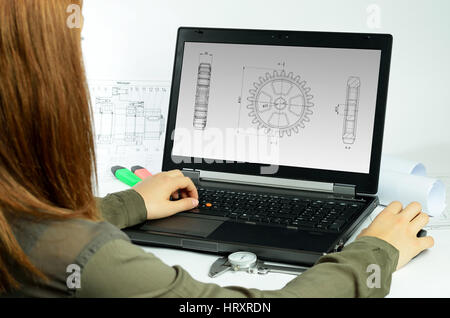 Young woman using CAD system in front of a laptop back view - Stock Photo