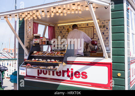Man making and selling poffertjes in Volendam roadside stall, The Netherlands - Stock Photo