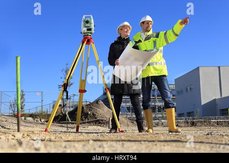 A Female Architect and surveyor on a construction site - Stock Photo