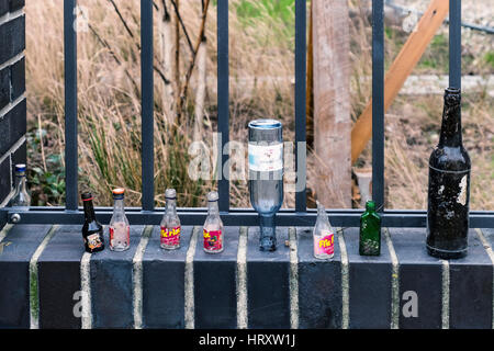 Berlin, Prenzlauer Berg. City still life. Empty alcohol, and wine bottles next to an urban park fence. Informal, - Stock Photo