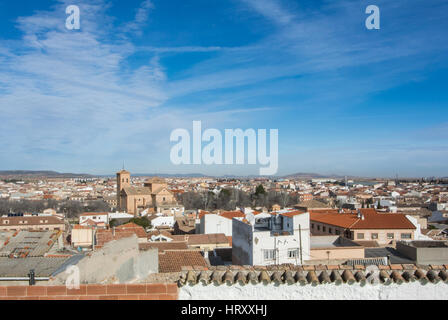 A panoramic view to spanish town Consuegra (Castilla-La Mancha) over the orange tile roofs on sunny day. - Stock Photo