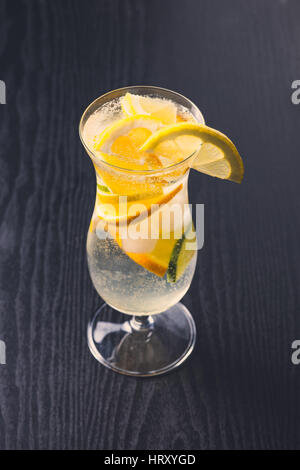 Fresh alcoholic drink with citrus fruits on dark wooden background - Stock Photo