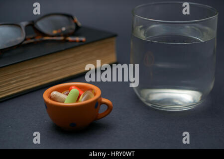 A pair of broken reader glasses resting on a closed book,  a bunch of pills in a bowl and a cup of water on dark - Stock Photo