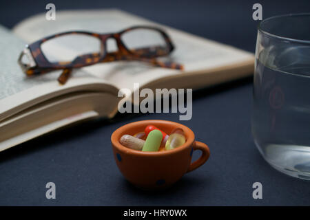 A pair of broken reader glasses resting on an old open book,  a bunch of pills in a bowl and a cup of water on dark - Stock Photo