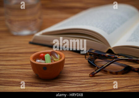A pair of broken reader glasses resting on an old open book,  a bunch of pills in a bowl and a cup of water on wooden - Stock Photo