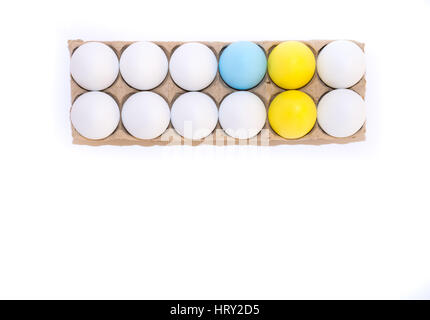 Two Easter eggs dyed yellow, one egg dyed blue and nine white hen's eggs in a tan cardboard carton from above on - Stock Photo
