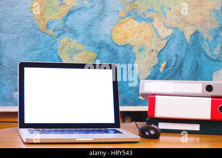 laptop computer with blank empty screen on world map background in business office - Stock Photo