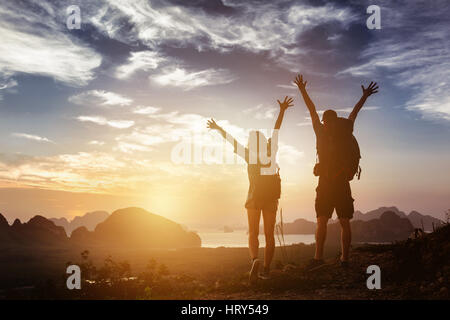 Happy couple stands in winner pose with rised arms on background of sunrise mountains and sea. Success concept - Stock Photo