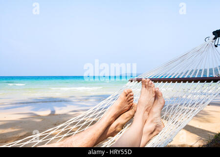family holidays on the beach, feet of couple in hammock, relaxation background - Stock Photo