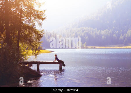 happy woman sitting on the pier and smiling, happiness or inspiration concept, enjoy life - Stock Photo