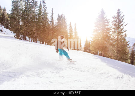 snowboarding in winter Alps, man with fast speed on snowboard in forest slope with backlight - Stock Photo