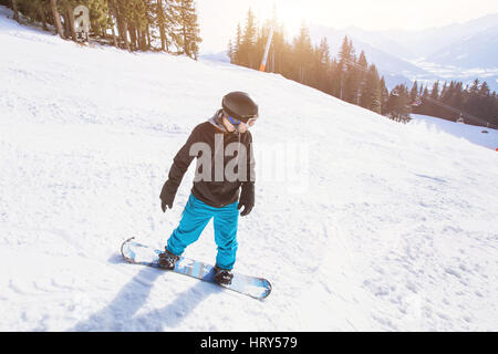 winter holidays, young man on snowboard in alpine mountains - Stock Photo