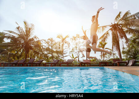 people jumping to the swimming pool, beach holidays, friends having fun together - Stock Photo