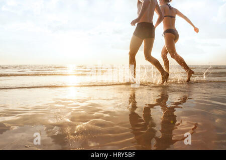 happy young couple running to the sea on the beach at sunset, silhouettes of man and woman, family holidays - Stock Photo