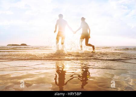 happy young couple having fun on the beach at sunset, water splash, enjoying life - Stock Photo