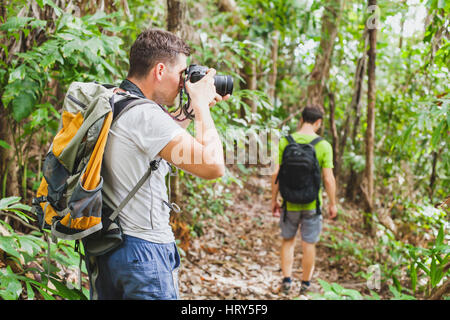 nature photographer in tropical jungle, group of tourists hiking in the forest, man taking photo with big camera - Stock Photo