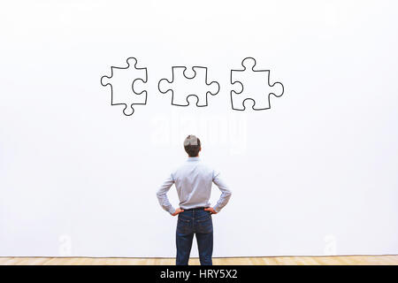 business solution concept, businessman looking at the pieces of puzzle - Stock Photo