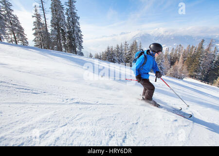 downhill skiing, skier going fast down the mountain, winter sport background - Stock Photo