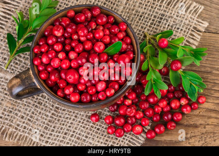 Cranberries over burlap background. Top view - Stock Photo