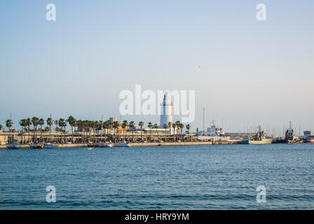 A view to a lighthouse La Farola, a promenade with palms and Mediterranean sea on the evening, Malaga, Andalusia, - Stock Photo