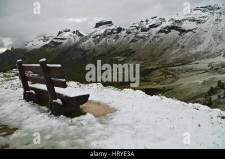 Passo Pordoi: bench covered by the first snow of the season on the Dolomiti mountains - Stock Photo