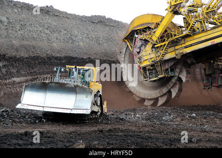 bulldozer and huge mining excavator wheel in brown coal mine - Stock Photo