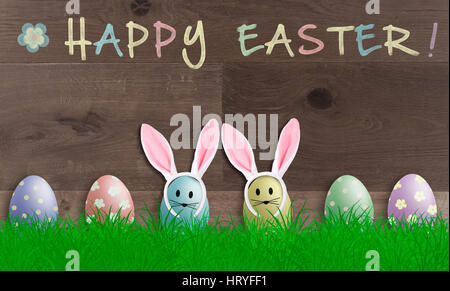 colorful pastel easter eggs with bunny ears on wooden background, promotional sign with text happy easter - Stock Photo